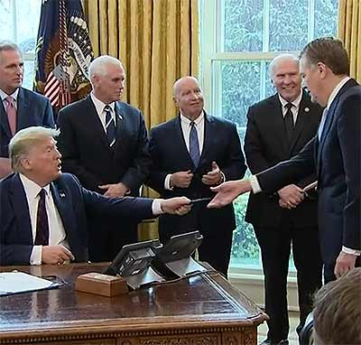 Trump handed out ceremonial signing pens to all the gathered Republicans..